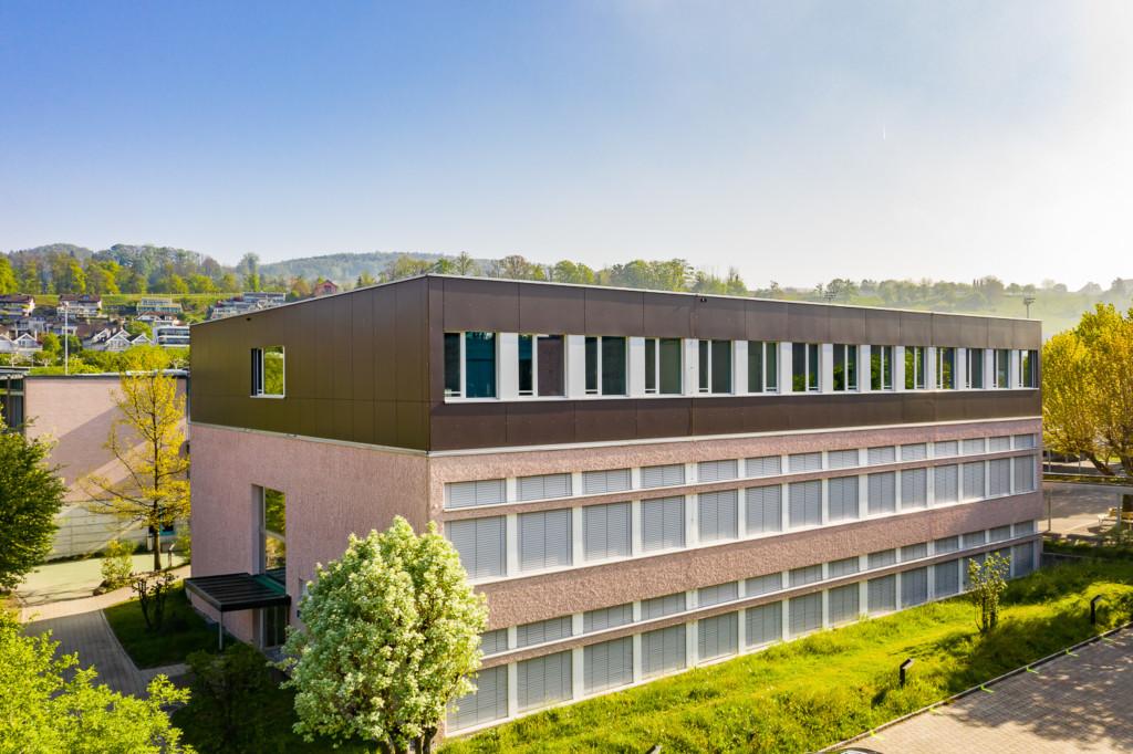 Schulhausaufstockung in Meilen: Vollkern-Fassade aus grossformatigen Fassadenplatten – nach Wunsch lackiert l Krattiger Holzbau AG Amriswil