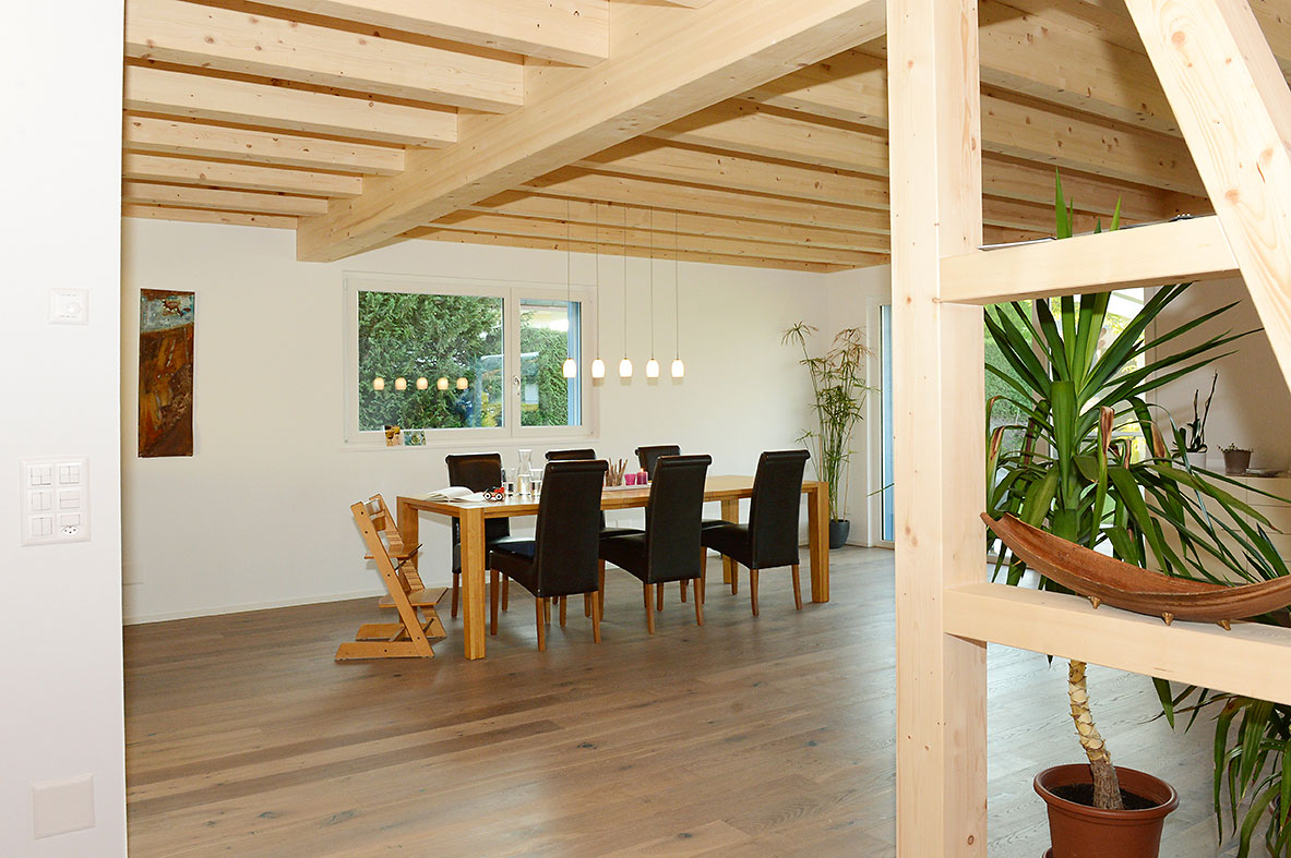 Renoviertes Wohnzimmer in Holz: Dachbalken, Tisch, Bodenparkett und Raumtrenner | Krattiger Holzbau AG Amriswil
